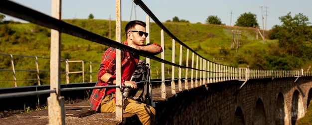 Mężczyzna siedzący na krawędzi mostu