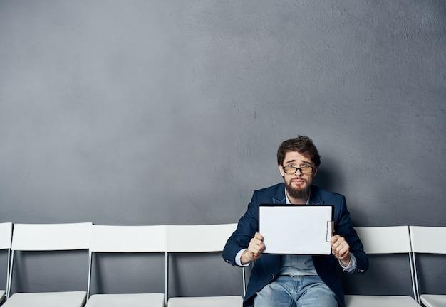 Mężczyzna siedzący na krześle czeka rozmowa kwalifikacyjna wznowić szkolenie zawodowe.