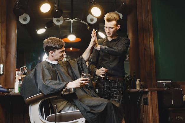 Mężczyzna siedzący na krześle. fryzjer z klientem. facet pije whisky.