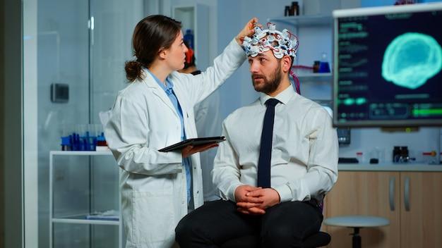 Mężczyzna siedzący na krześle neurologicznym z zestawem słuchawkowym do skanowania fal mózgowych, lekarz badacz śledzący ewolucję mózgu pacjenta za pomocą tabletu, dostosowujący urządzenie eeg. naukowiec badający układ nerwowy.