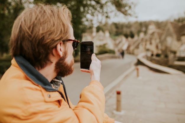 Mężczyzna siedzący na ławce i robiący zdjęcia telefonem w wiosce
