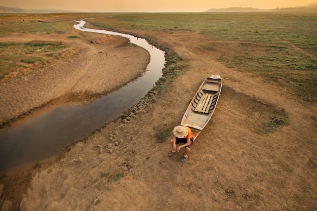 Mężczyzna siedzący na łodzi w pobliżu suszącej rzeki