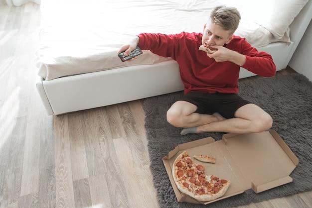Mężczyzna siedzący na podłodze w pokoju z pudełkiem pizzy i przełączaniem kanałów telewizyjnych