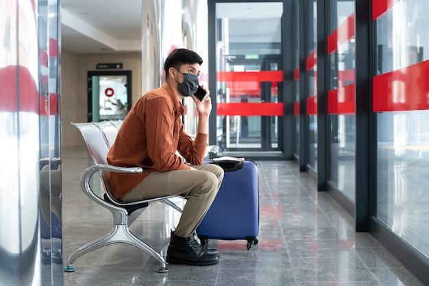 Mężczyzna Siedzący Na Stacji Rozmawia Przez Telefon Komórkowy Premium Zdjęcia