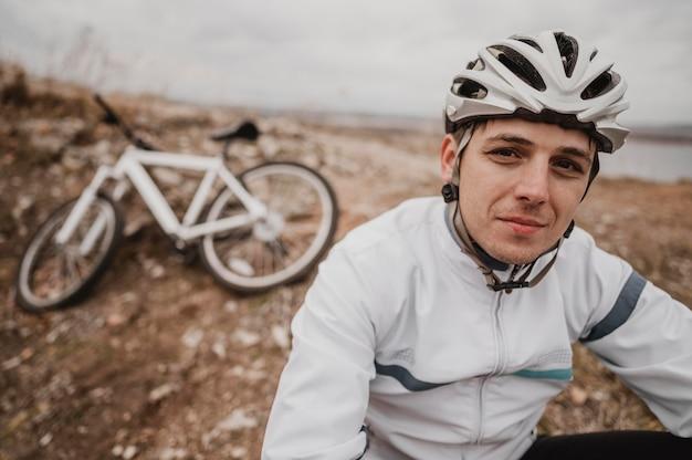 Mężczyzna siedzący na trawie obok swojego roweru górskiego