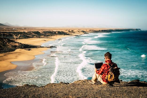 Mężczyzna siedzący na wybrzeżu pracuje z laptopem