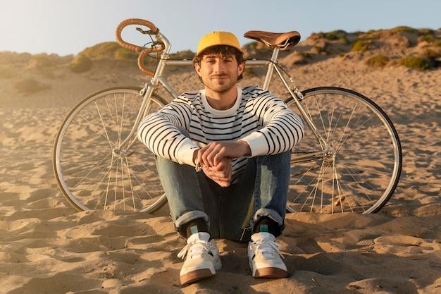 Mężczyzna siedzący nad morzem pełne ujęcie