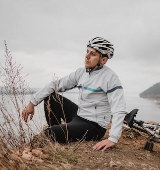 Mężczyzna siedzący obok swojego roweru górskiego