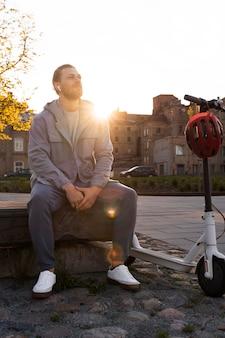 Mężczyzna siedzący obok swojego skutera