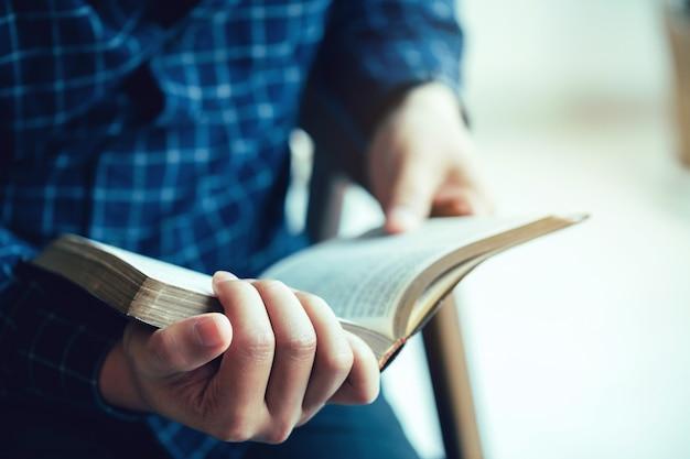 Mężczyzna siedzący podczas czytania biblii lub książki nad betonową ścianą przy świetle okna