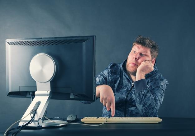 Mężczyzna siedzący przy biurku, patrząc na ekran komputera