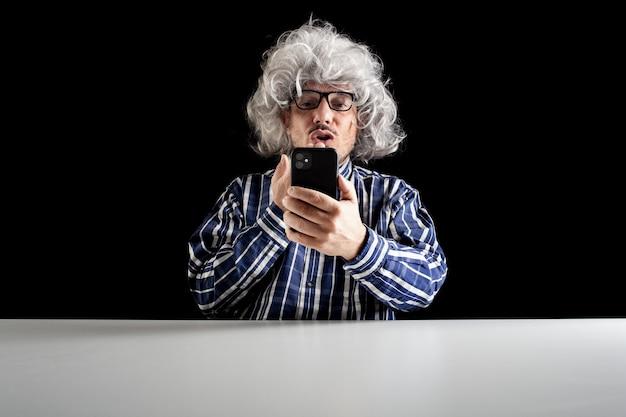 Mężczyzna siedzący przy biurku, posyłający buziaka, prowadzący wideoczat za pomocą smartfona na czarnym tle