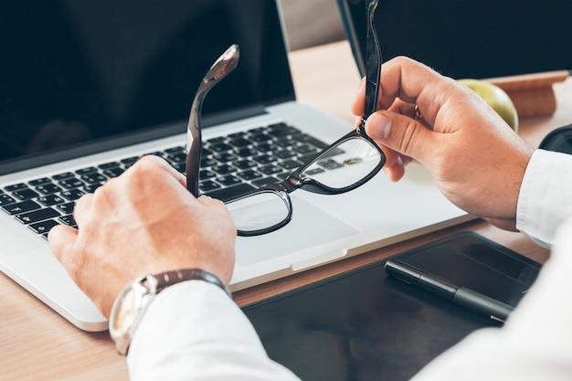 Mężczyzna siedzący przy biurku w domu i trzymający okulary,