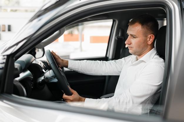 Mężczyzna siedzący przy salonie samochodowym kierownicy i patrząc uważnie.