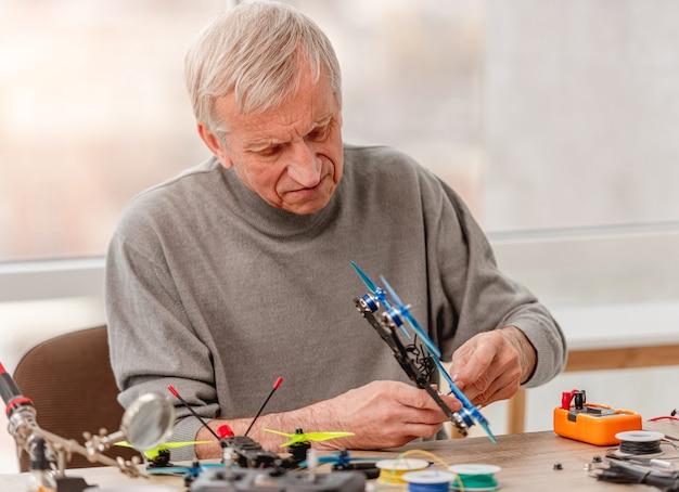 Mężczyzna siedzący przy stole i trzymając w rękach drona quadcoptera podczas procesu naprawy