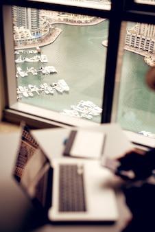Mężczyzna siedzący przy stole obok okna ze wspaniałym widokiem na łodzie i miasto.