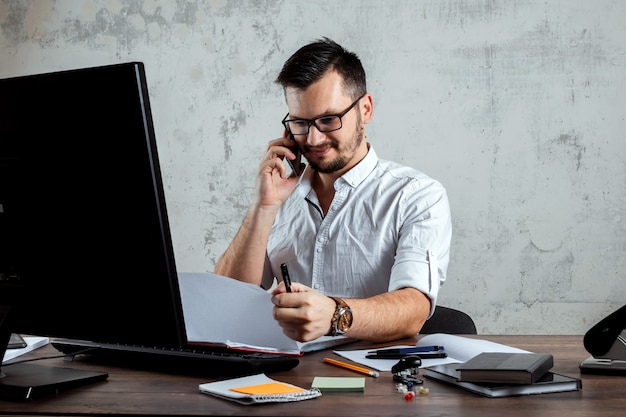 Mężczyzna siedzący przy stole w biurze, rozmawia przez telefon, decyduje ważne pytanie. koncepcja pracy biurowej, startup. skopiuj miejsce.