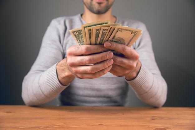 Mężczyzna siedzący trzymając pieniądze w dłoniach