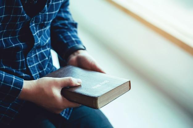 Mężczyzna siedzący trzymający biblię lub książkę nad betonową ścianą ze światłem w oknie