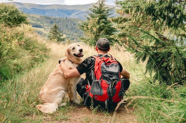 Mężczyzna siedzący tyłem na górskim szlaku trekkingowym obok psa golden retriever