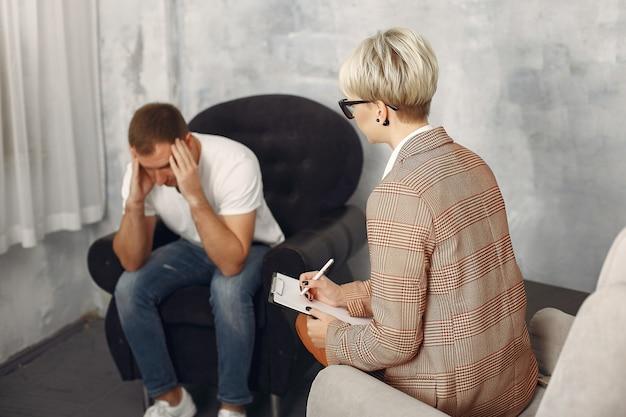 Mężczyzna siedzący w biurze psychologa i rozmawiający o problemach