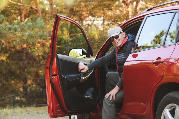 Mężczyzna siedzący w czerwonym samochodzie z otwartymi drzwiami wejściowymi