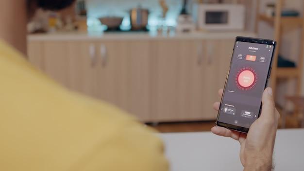 Mężczyzna siedzący w domu z systemem automatyki oświetleniowej, trzymający smartfona