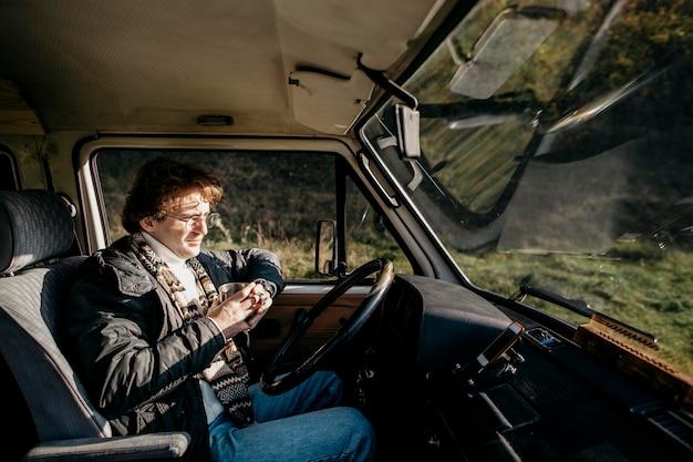 Mężczyzna siedzący w furgonetce i patrząc na zewnątrz