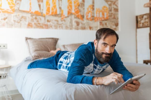 Mężczyzna siedzący w łóżku zrelaksowany w domu na stole