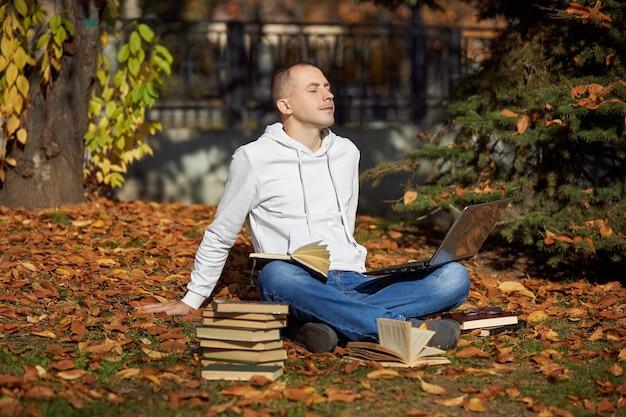 Mężczyzna siedzący w parku z laptopem notatnik książki i podręczniki odkrywanie dystansu społecznego uczenia się