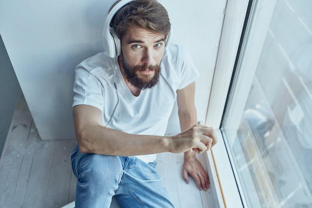 Mężczyzna siedzący w pokoju z technologią słuchawek