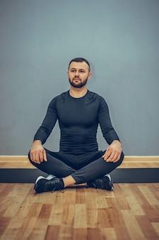 Mężczyzna siedzący w pozycji jogi lotosu