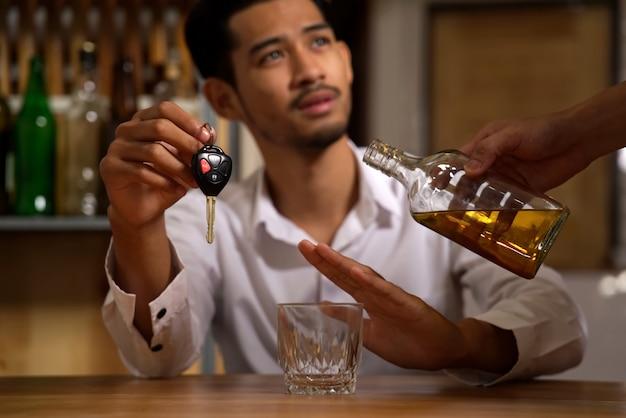Mężczyzna siedzący w restauracji, trzymający kluczyk w samochodzie, odmawiający alkoholu swojemu przyjacielowi.
