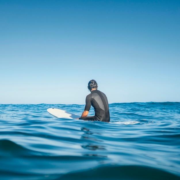 Mężczyzna siedzący w wodzie od tyłu