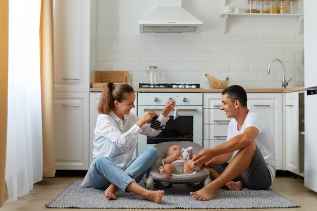 Mężczyzna siedzący z żoną i noworodkiem chłopca lub dziewczynki w bujanym fotelu na podłodze w kuchni. urocza młoda trzyosobowa rodzina bawi się rano, spędzając razem czas w domu.