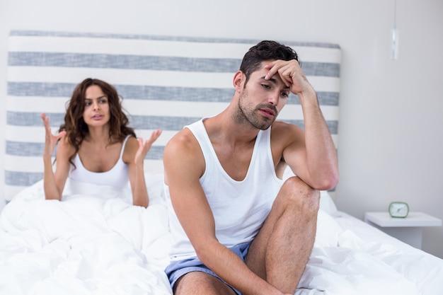 Mężczyzna siedzi, a żona krzyczy na niego