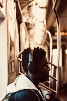 Mężczyzna siedzi i nosi słuchawki wewnątrz pociągu