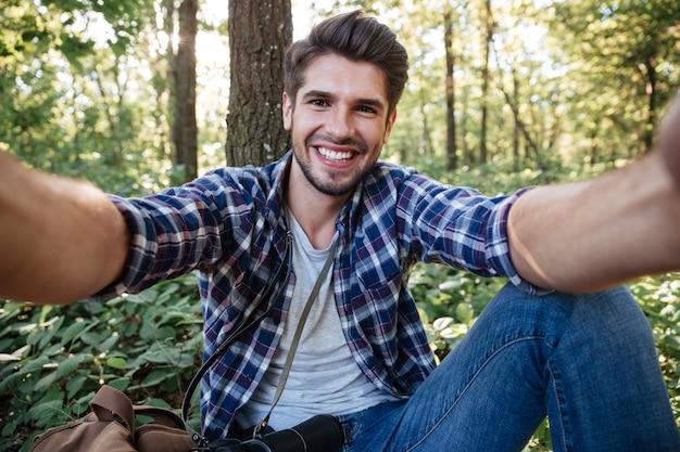 Mężczyzna siedzi i robi selfie w lesie