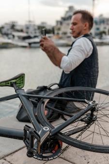 Mężczyzna siedzi i robi zdjęcie obok swojego roweru