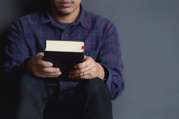 Mężczyzna siedzi i trzyma biblię. biblia, modlitwa, mężczyźni.