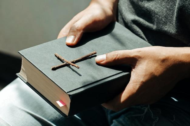 Mężczyzna siedzi i trzyma biblię