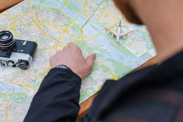 Mężczyzna siedzi i wskazując na mapie