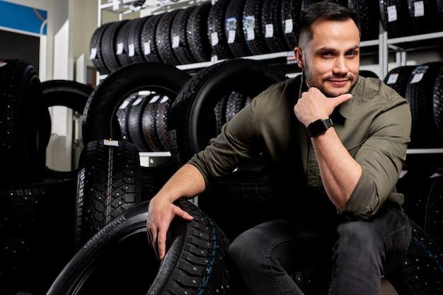 Mężczyzna siedzi i zastanawia się, które opony kupić, kaukaski facet w codziennym stroju siedzi w kontemplacji w warsztacie samochodowym, otoczony czarnymi oponami do samochodu