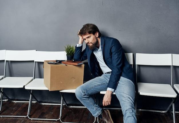 Mężczyzna siedzi na białym krześle czekając na depresję w poszukiwaniu pracy pole oświetlenia