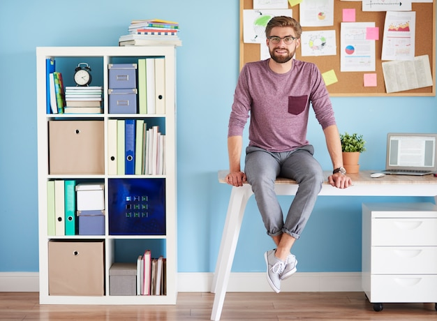 Mężczyzna siedzi na biurku w domowym biurze