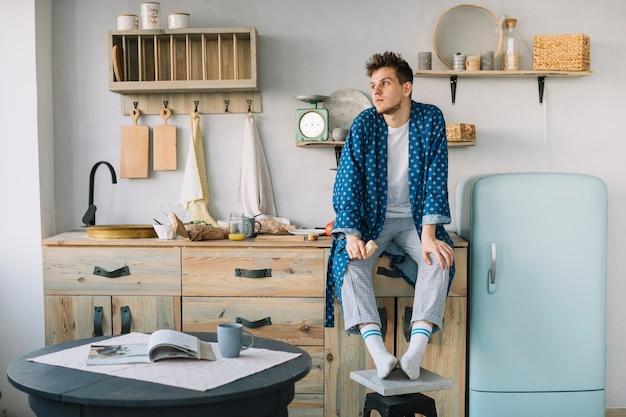 Mężczyzna siedzi na blacie kuchennym gospodarstwa żywności