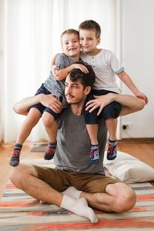 Mężczyzna siedzi na dywanie, niosąc dwóch synów na ramieniu
