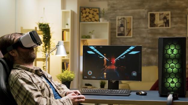 Mężczyzna siedzi na fotelu do gier, grając w gry wideo za pomocą zestawu słuchawkowego vr z bezprzewodowym kontrolerem.