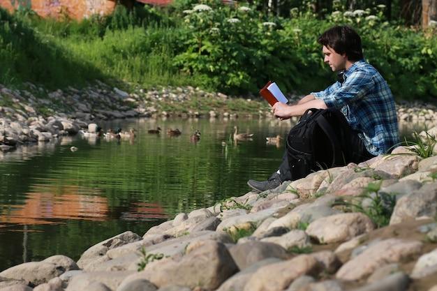 Mężczyzna siedzi na kamiennej rzece