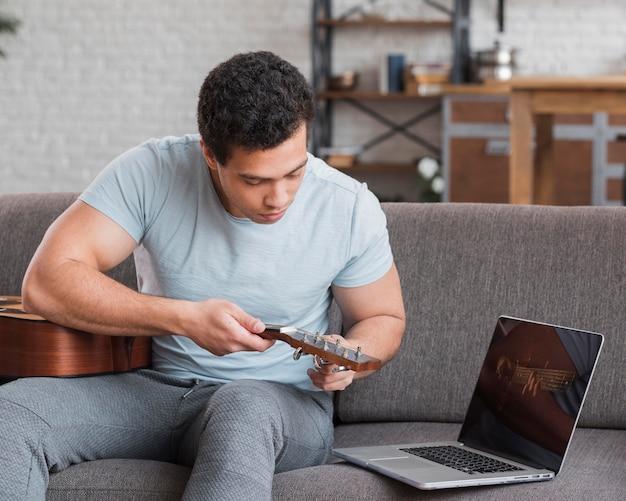 Mężczyzna siedzi na kanapie i strojenie gitary